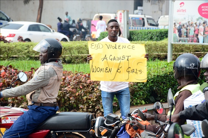 young man from the afer ities roject of lan nternational ganda displays messages to boda boda cyclists along ampewo oundabout in ampala as part of the activities to mark the launch of the 16 ays of ctivism ampaign against gende rbased violence hoto by ddie sejjoba