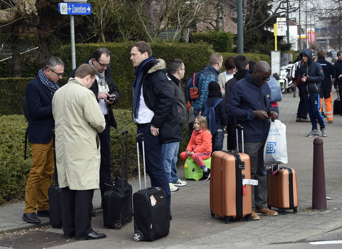 assengers are gathered near russels airport in aventem following its evacuation after at least 13 people were killed and 35 injured as twin blasts rocked the main terminal of russels airport  hoto