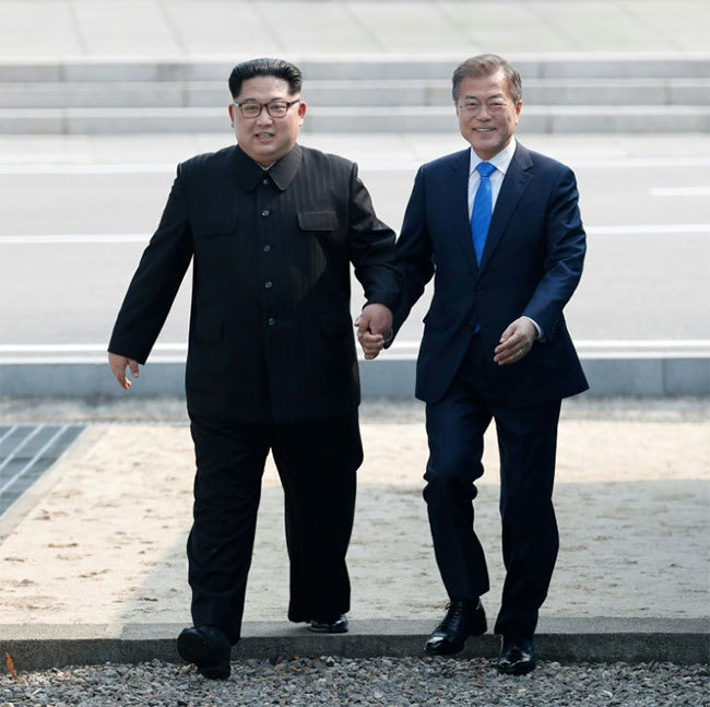 orth oreas leader im ong n  and outh oreas resident oon aein held hands as they stepped over the ilitary emarcation ine that divides their countries orea ummit ress ool