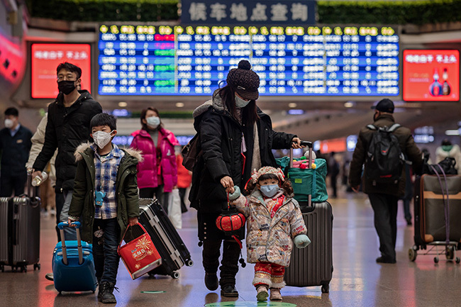 girl  wearing a face mask holds the finger of her mom and a lantern as they travel back home for the unar ew ear holidays at eijing est ailway tation in eijing on anuary 24 2020 hoto by