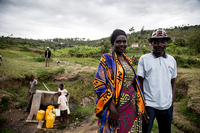 eanlaude utarindwa 42  a utu and aphrosa ukarubayize 57 a utsi woman pose for a photo near a wellspring that sits in the valley that separates their villages at the border between usambira and yarubaka sectors of amonyi istrict