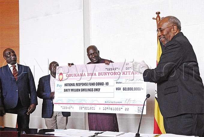 fficials from unyoro itara ingdom led by ndrew yakutaga centrehanding over a sh60m cheque to rime inister uhakana ugundahoto by icholas neal