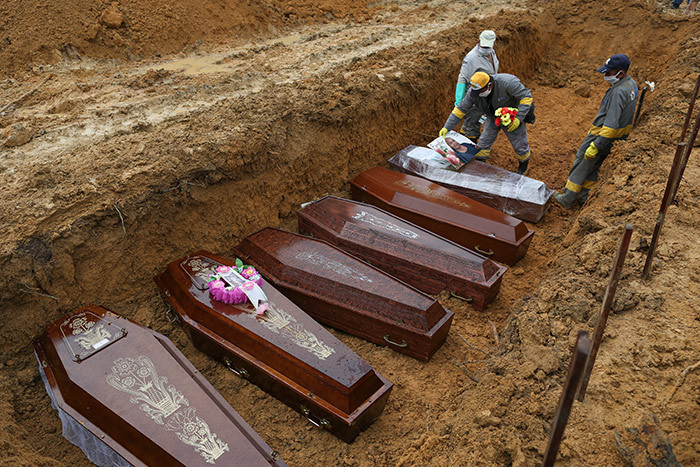 emetery workers prepare the coffins to be buried in a mass grave at the ossa enhora cemetery in anaus mazon state razil on ay 6 2020 amid the 19 coronavirus pandemic hoto by