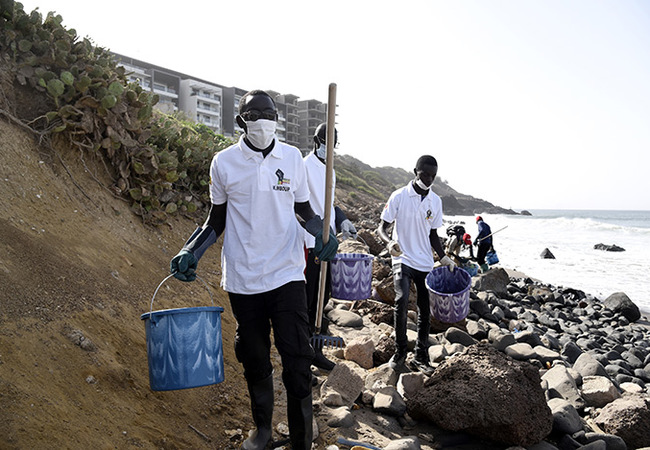 olunteers and workers wearing protective gear carry buckets and shovels as they arrive to pick up waste during a cleanup operation of medical trash thrown away by nearby hospitals on the apanuel beach in akar on ebruary 29 2020 hoto by eyllou