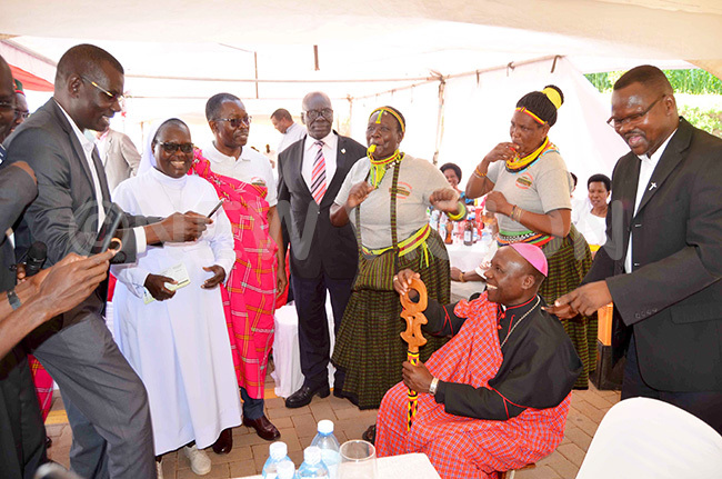 hristians from oroto and otido diocese cheer as ishop ciru gets a feel of the arimojong stool that they donated to him