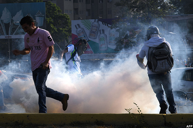 enezuelans run away from tear gas during running battles with security forces in aracas on uesday