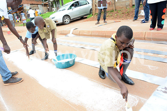 upils of atete unior chool eft to right rispus yambadde saac upanzi and yprian yombi painting the ebra crossing on atete oad near their school during the launch of road safety dangers campaign in atete akiso district recently