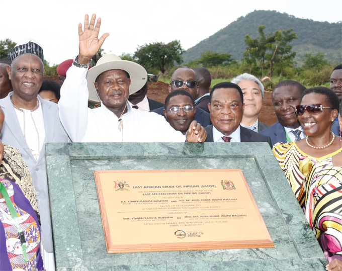 resident useveni flanked by unyoro king olomon guru left anzanias minster of foreign affairs ugustine hilip ahiga secondright and energy minister rene uloni right laying the foundation stone at the starting point of the ast frican rude il ipeline in oima
