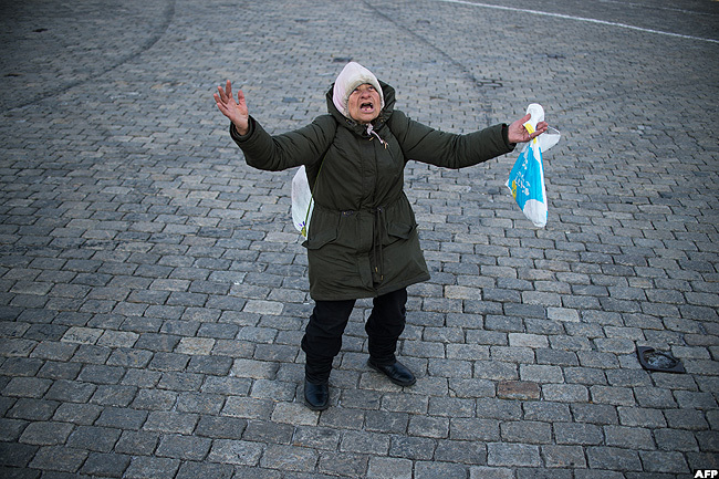 woman prays in front of the golden domed lexander evsky athedral in ulgaria