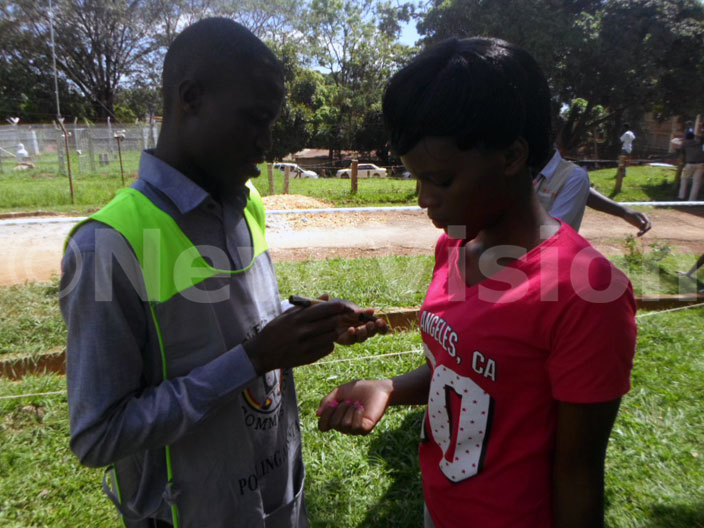 n election officer marking the thumb of a female voter who has justed casted her vote icture by lfred yenkya