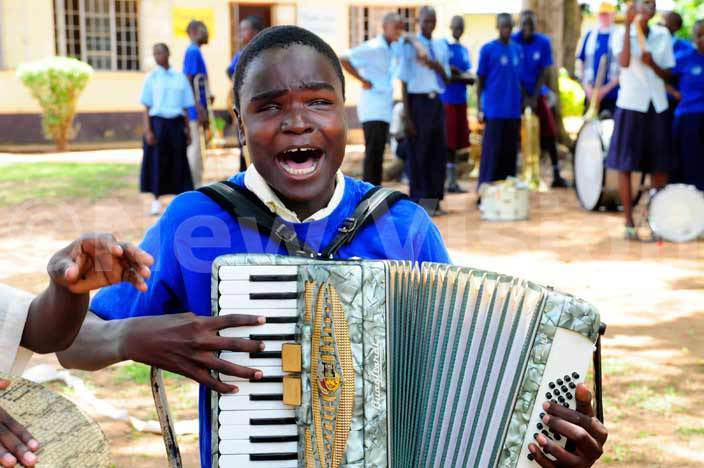pupil plays an acordian at the function to commission a water system for the blind children at madera in oroti hoto by dide sejjoba