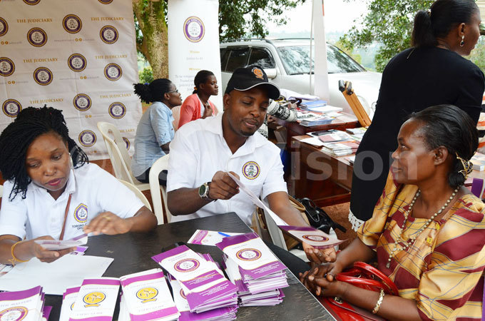 olomon uyita the ommunications officer of the judiciary gives legal  information to a lady during the camp