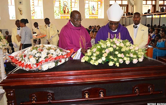 ishop aul semwogerere  wearing a white mitre and sgr ohn aptist auta placing a wreath pn the casket of r imon agugube during the requiem mass at t harles wanga atholic hurch tinda on onday ebruary 17 hoto by athias azinga