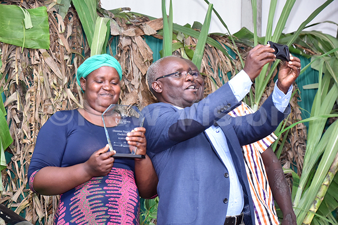 ision roup  obert abushengacentre takes a selfie with winner hamim apakol while holding her award