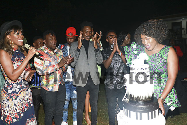 amakula cutting her birthday cake as her family and fellow artistes sang for her
