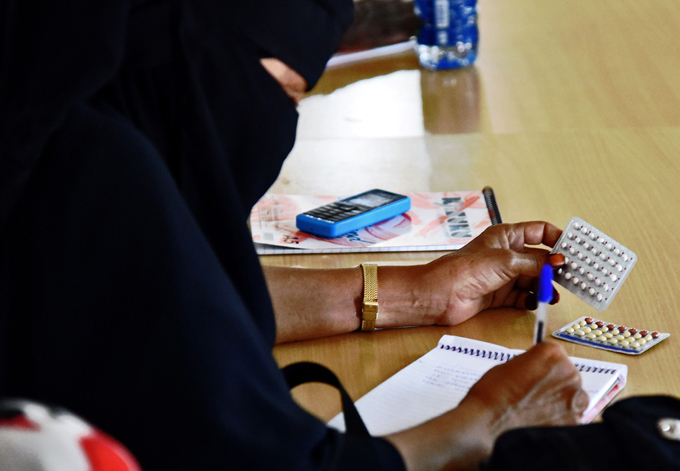 female religious leader takes notes during a session at the local maternity facility on what slam allows and does not allow in terms of family planning and on the benefits of family planning in ajir own  hoto