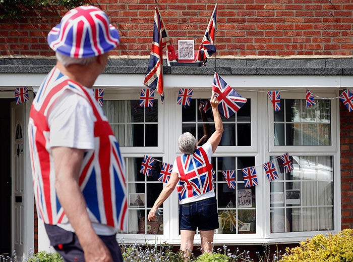 raham looks on as his wife ue illson untangles a flag on their roof on their home ahead  a 2 minute silence to mark the 75th anniversary of  ay ictory in urope ay the end of the econd orld ar in urope in artley intney ampshire on ay 8 2020 hoto by