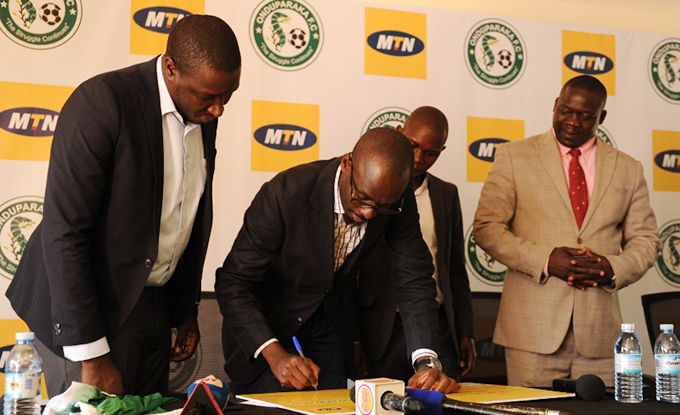 atin ebuliba  gandas senior manager brand and communications signs the cheque to symbolise the sponsorship ourtesy hoto