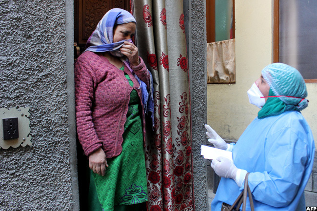 medical worker talks with a resident during a door to door campaign to check any possible contact with a local woman