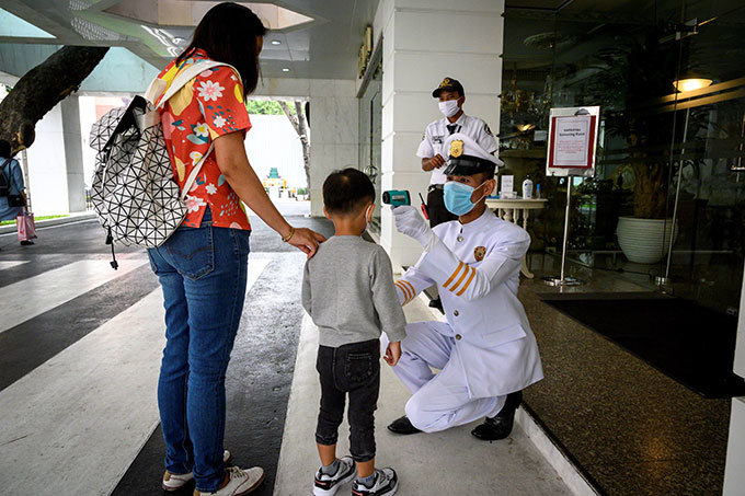 ecurity personnel take the temperature of people entering a building as part of measures to combat the spread of the 19 novel coronavirus in angkok on arch 16 2020 hoto