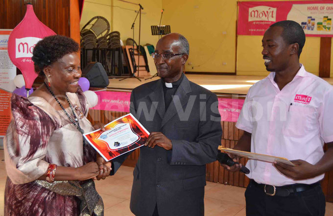 on arah konge receives a certificate for the choir of ansanga atholic parish from r elix umuhaise