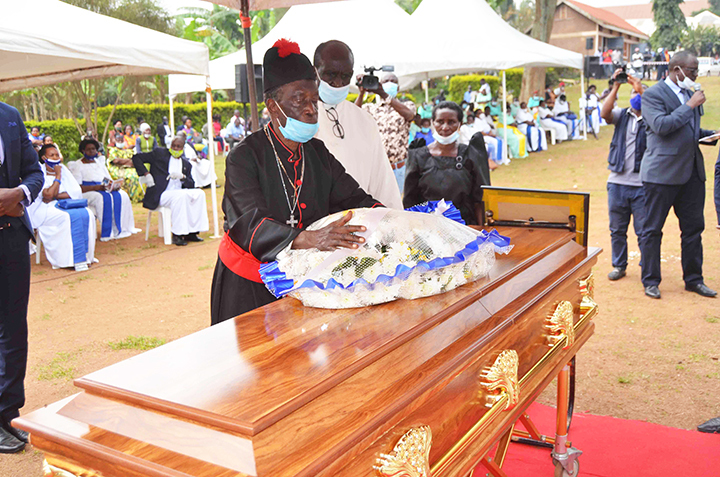 Canon James Lutaaya Ddungu (right) lays a wreath on the casket of his wife Ruth Nambweere Ddungu during the funeral service at Martyrs Anglican Church Busega (Rubaga Division). Photo by Mathias Mazinga