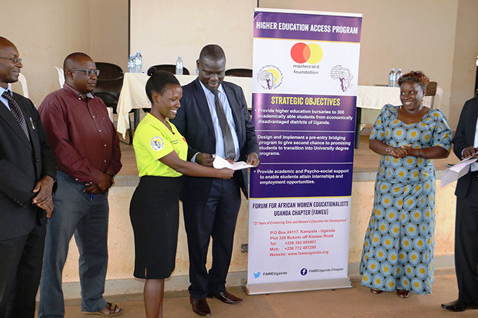 he hief uest rof eorge ada penjuru the ice hancellor of ulu niversity handing a bursary award letter to one of the students looking on is rs rene iizanyango the  ganda oard ember and other guests
