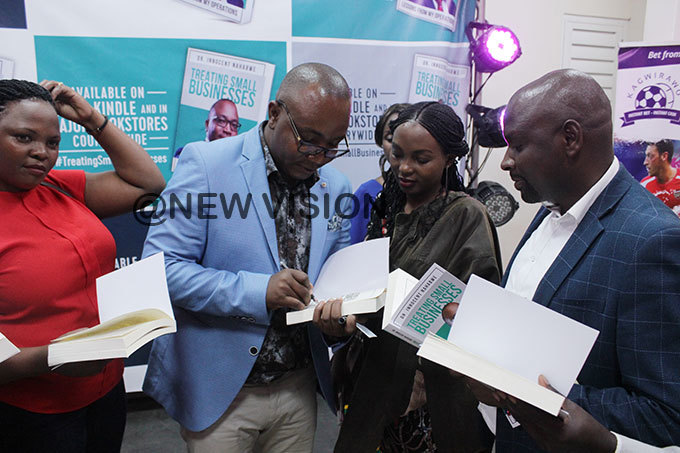 ahabwe signing books for his readers hoto by enis subuga
