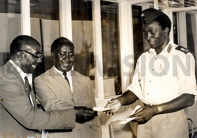 r amson isekka presents a cheque to the ational hairman of nternational lympic ommittee aj en rancis yangweso to take the ational team to the olympics