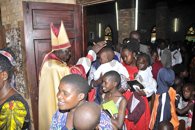 ishop ames illiam sebaggala blessing children after the aster unday service at aints hilips  ndrews athedral in ukono hoto by enry subuga