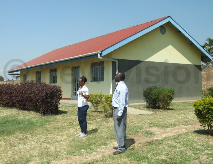 he deputy head teacher harles ndoga showing off the new buildings