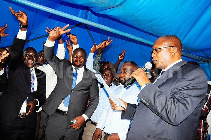 ubarak unyagwa flashes  party victory symbols after he was nominated at the party headquarters in ajjanankumbi ampala