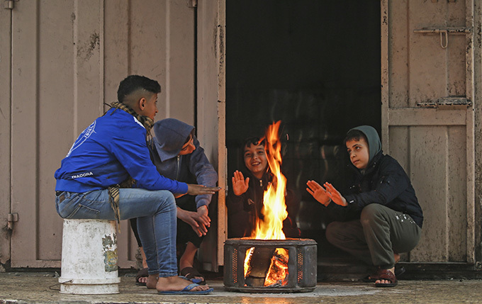 alestinian youths warm themselves around a fire during heavy rain in aza ity on ecember 27 hoto by