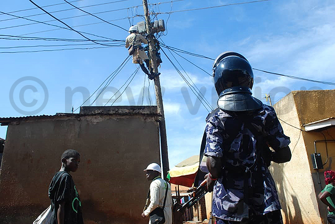 olice officer looking on as meme engineers check for wires and meters that were illegally connected y awrence ulondo