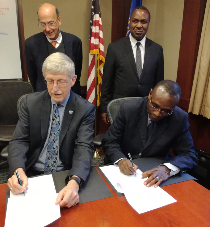 r rancis ollins and r eter demere sign the o while r oger lass and r lioda umwesigye look on in