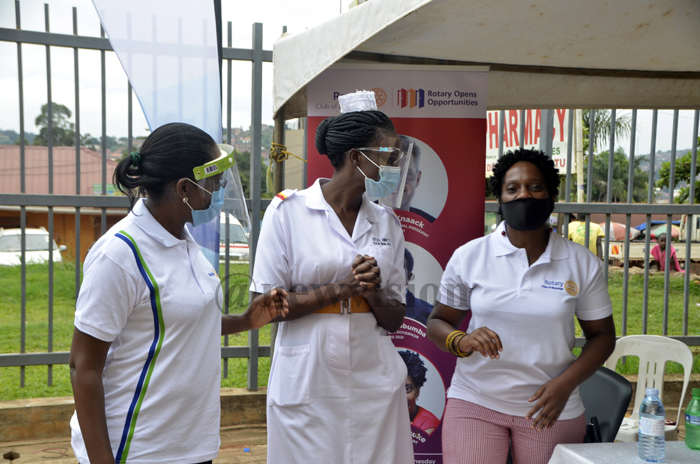 Rotarians and medics interact during the hand over of the 350 face shields to Kiruddu Hospital in Kampala