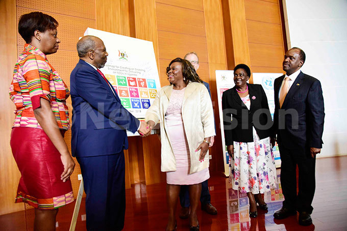 rime inister of ganda uhakana ugunda second left talks to  esident oordinator osa alango centre  irector oachim arker third right tate inister eneral uties ary kurut second right and ustainable evelopment oals mbassador atrick itature  after launching the ational ustainable evelopment oals oadmap while   esident oordinator in ganda osa alango looks on during the launch of the roadmap  at the rime inisters ffice in ampala on ctober 23 2018 hoto by ennedy ryema