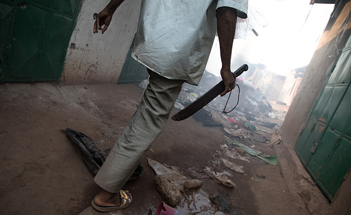 man holding a machete walks between ransacked houses in the 5 district in angui on ecember 26 2019 after clashes erupted when traders took up arms to oppose taxes levied by militia groups t least 11 people were killed in fighting between militiamen and traders in a restive district of angui the capital of the entral frican epublic two security officials and an imam said on ecember 26 2019 he security sources said between 11 and 14 people died after clashes erupted late on ecember 25 2019 while the imam wad l arim said 16 bodies had been brought to the local li abolo mosque hoto by