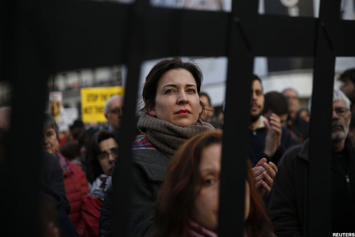 eople stand behind a mock border fence during a protest against the urkey migrant deal in adrid pain euters