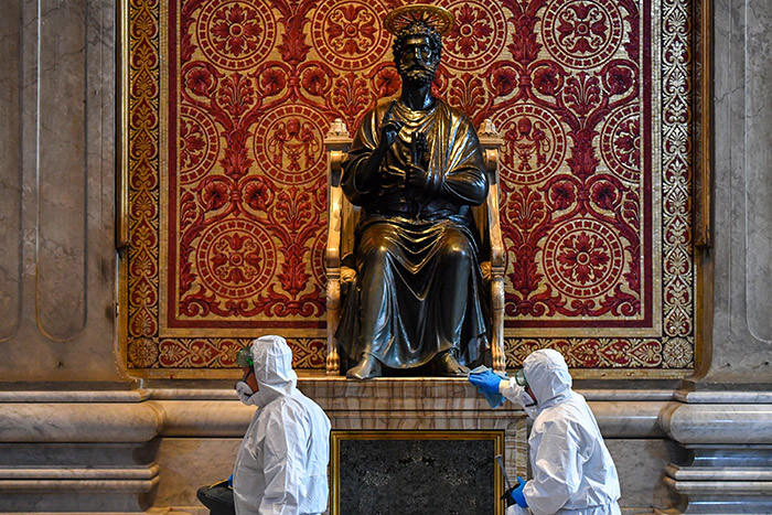 en wearing protective overalls and mask clean the statue of t eter during the sanitation of t eters asilica in he atican on ay 15 2020 during the lockdown aimed at curbing the spread of the 19 infection caused by the novel coronavirus hoto by lberto
