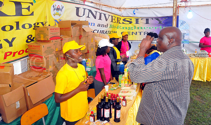 hamed ilder explains to a client some of the products made by akerere niversity ood science at the trade show ampala ct 5 2016hoto by ilfred anya