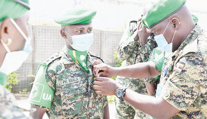 A senior military officer pinning a medal on a Battle Group 27 officer
