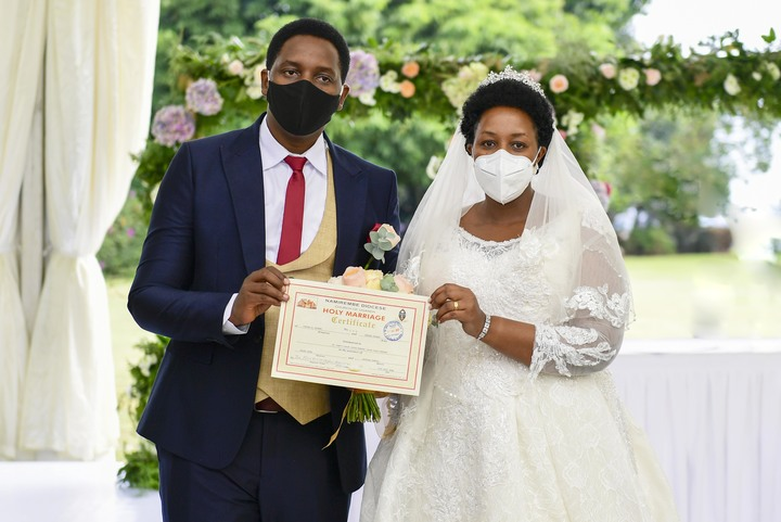 We did it: The couple displays a marriage certificate