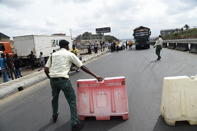 n officer of gun tate oad afety ommand tries to block the expressway to prevent a truck driving into agos at the joduerger border between agos and gun tates on arch 31 2020 following the lockdown by the authorities to curb the spread of the 19 coronavirus
