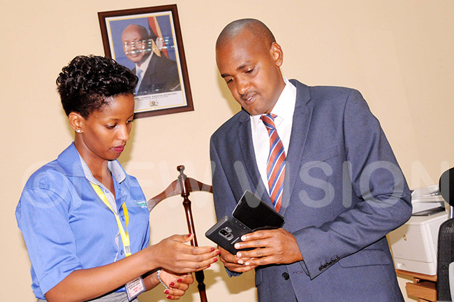 korion gronomist ichard uwanyesiga shows the pp to minister umwebaze