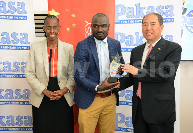 ew ision oard of overnors haiperson onica hibita and the hinese ambassador to ganda  heng hu iang hand over an award to tephen sembuya at the akasa oung nterprenuer awards 2018 held at the olden ulip otel in ampala on 29 ctober 2018