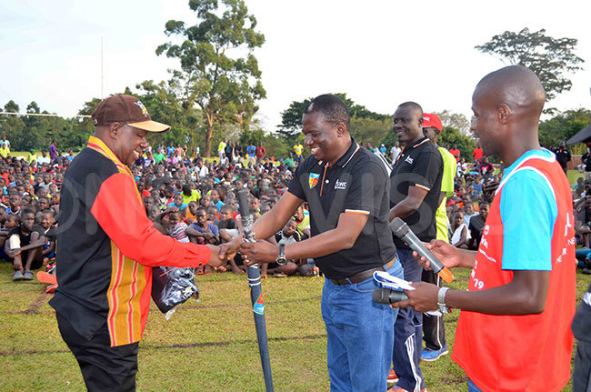 he state minister for sports harles akkabulindi left receiving souvenirs from the head teacher of amilyango ollege onstantine puuga