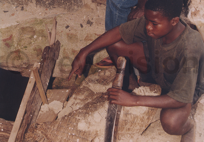 boy points out the opening of a pit at one of the abandoned houses where more bodies were found ile hoto