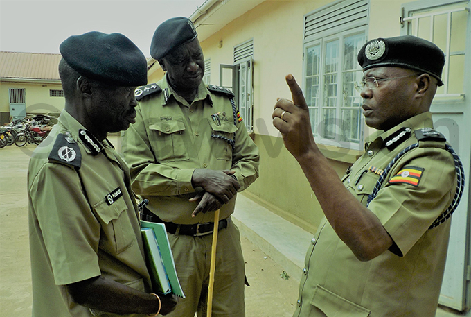 ssistant nspector eneral of olice san asingye right speaks to the regional olice commander oroto ichard aruk centre after unveiling a policy whereby all olice personnel will have to work in aramoja as their first deployment for at least two years hoto by landason anyama