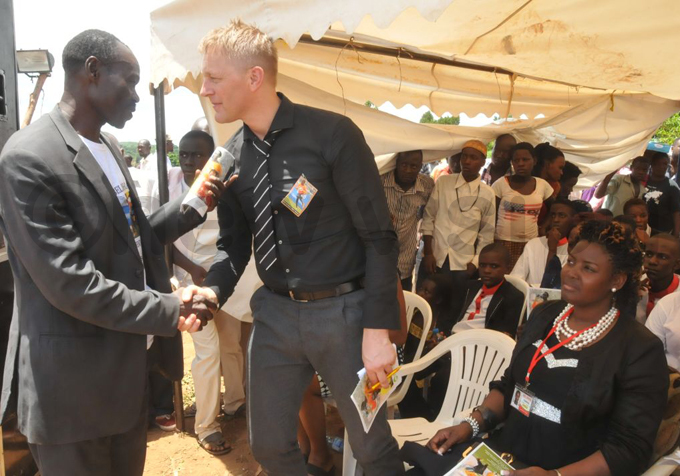 coach eimir allgrimsson chats with haira nr at the ceremony at uyuga illage in agando ayuge istrict hoto by onald iirya